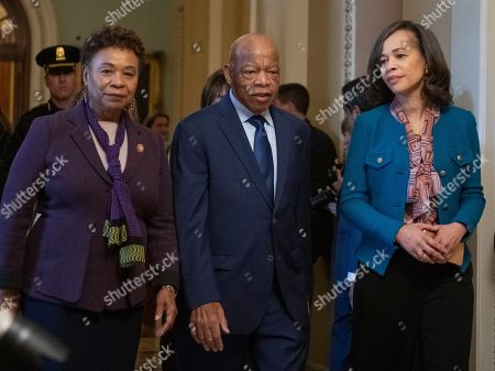 Stock Picture of United States Representatives Barbara Lee (Democrat of California), left, John Lewis (Democrat of Georgia), center, and Lisa Blunt Rochester (Democrat of Delaware), right, depart the US Senate Chamber after joining their US House Democratic colleagues in witnessing two votes on legislation to reopen the government in the US Capitol in Washington, DC.