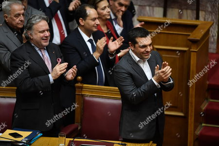 Greece's Prime Minister Alexis Tsipras, right, accompanied by Greek Alternate Minister of Foreign Affairs George Katrougalos, left, and other members of his government applaud following a vote that ratified the Prespa Agreement at the parliament in Athens, . Greek lawmakers have ratified the agreement for the country to drop its objections to neighbouring Macedonia joining NATO if the small country's name is changed to North Macedonia.The ratification vote came after three days of acrimonious debate on the deal, which aimed to end a nearly three decade-long dispute that has kept Macedonia from joining the western military alliance and the European Union