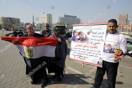 A man holds a picture of Egyptian President Abdel Fattah al-Sisi embracing a police officer who died in November 2018 of his wounds after a facial reconstruction operation following an attack in August 2013, in Tahrir Square, Cairo, Egypt, 25 January 2019 on the eighth anniversary of the uprising that toppled former President Hosni Mubarak. More than 800 people were killed and thousands injured during the 18-day uprising against the Egyptian regime which led to the removal of President Hosni Mubarak on 11 February 2011.