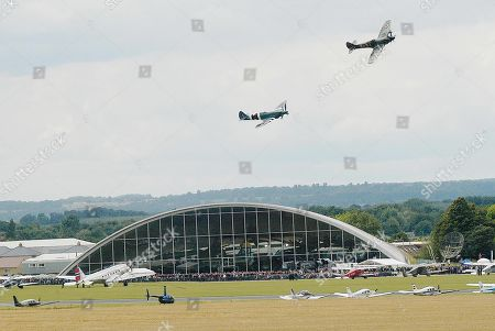 A pair of world war two Royal Air Force Super Marine spitfires fly over the Sir Norman Foster designed American Air Museum at Imperial War Museum Duxford aerodrome in Cambridge during an airshow.
