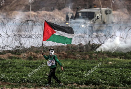 A Palestinian protester youth wearing a Guy Fawkes mask carries the poster of Palestinan late leader Yasser Arafat and Hamas late leader Sheikh Ahmed Yassin next to Israeli troopss during the clashes that erupted after Friday protests near the border between Israel and Gaza Strip, in East Gaza, 25 January 2019. One Palestinian protester reportedly was shot dead and more then 50 others were injured during the clashes in the eastern Gaza Strip. The Palestinians protesters plan to call for the right of Palestinian refugees across the Middle East to return to their homes they fled in the war surrounding the 1948 creation of Israel.