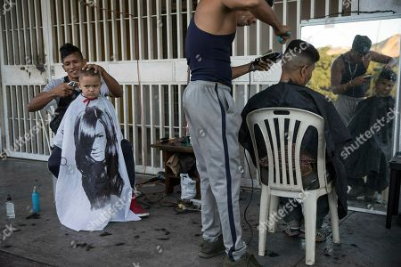 Juan Manuel Marquez, 32, left, cuts the hair of Jean Pierre, 4, at a makeshift barber shop on a sidewalk in Caracas, Venezuela, . Juan Manuel charges 1000 bolivars or around .50 cents US for each service. Juan Guaido, the Venezuelan opposition leader who has declared himself interim president appeared in public Friday for the first time in days and vowed to remain on the streets to usher in a transitional government, while President Nicolas Maduro dug in and accused his opponents of orchestrating a coup