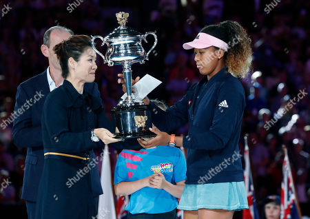 Retired tennis champion Li Na (L) of China presents Naomi Osaka (R) of Japan with her trophy after Osaka won the women's singles final match against Petra Kvitova of Czech Republic at the Australian Open Grand Slam tennis tournament in Melbourne, Australia, 26 January 2019.