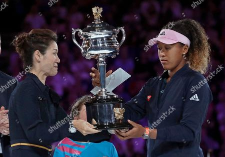 China's Li Na presents the Daphne Akhurst Memorial Cup to Japan's Naomi Osaka, right, after she defeated Petra Kvitova of the Czech Republic in the women's singles final at the Australian Open tennis championships in Melbourne, Australia