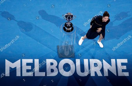 China's Li Na brings the Daphne Akhurst Memorial Cup to the court ahead of the women's singles final at the Australian Open tennis championships in Melbourne, Australia