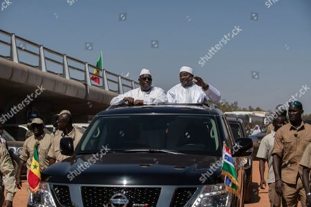On, Senegal's President Macky Sall, center left, and Gambian President Adama Barrow, center right, drive past a newly inaugurated bridge in Banjul, Gambia. The leaders of Senegal and Gambia have cut the ribbon on a project that was decades in the making, a bridge that links the north and south banks of the Gambia River and ties the neighbors closer together. A boom in trade is expected for this part of West Africa