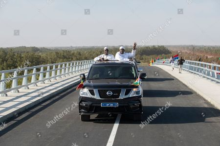 On, Senegal's President Macky Sall, left, and Gambian President Adama Barrow, right, drive on a newly inaugurated bridge in Banjul, Gambia. The leaders of Senegal and Gambia have cut the ribbon on a project that was decades in the making, a bridge that links the north and south banks of the Gambia River and ties the neighbors closer together. A boom in trade is expected for this part of West Africa
