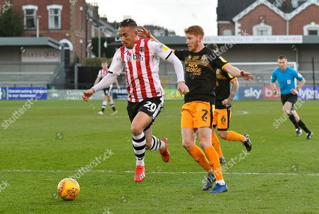 Stock Image of Kane Wilson (20) of Exeter City battles for possession with Brad Halliday (2) of Cambridge United during the EFL Sky Bet League 2 match between Exeter City and Cambridge United at St James' Park, Exeter