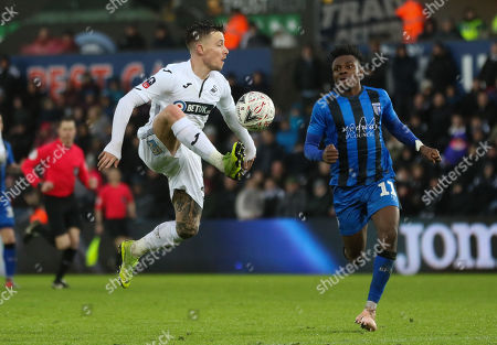 Barrie McKay of Swansea City wins the ball as Regan Charles-Cook of Gillingham closes in