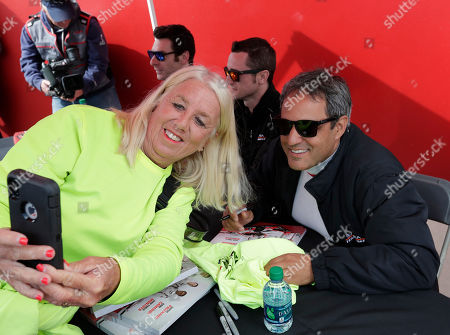 A race fans takes a selfie photo with driver Juan Pablo Montoya, right, during an autograph session before the start of the IMSA 24 hour auto race at Daytona International Speedway, in Daytona Beach, Fla