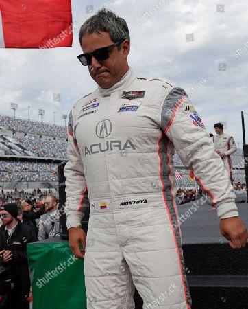 Juan Pablo Montoya, of Colombia, walks to his car before the IMSA 24-hour race at Daytona International Speedway, in Daytona Beach, Fla