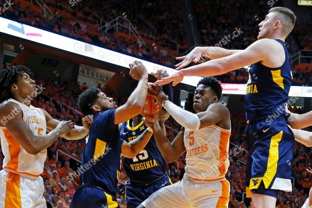 Tennessee guard Admiral Schofield (5) goes for a shot as he's defended by West Virginia guard Jermaine Haley, left, and forward Logan Routt, right in the first half of an NCAA college basketball game, in Knoxville, Tenn
