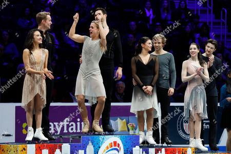 Madison Chock and Evan Bates, left, who placed second, watch Madison Hubbell and Zachary Donohue, who won, react on the medal stand for ice dancing, next to Kaitlin Hawayek and Jean-Luc Baker, third place, and Lorraine McNamara and Quinn Carpenter, fourth place, at the U.S. Figure Skating Championships, in Detroit