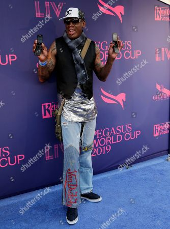 Dennis Rodman poses with two flip telephones on the blue carpet at the Pegasus World Cup Invitational Horse Race, at Gulfstream Park in Hallandale Beach, Fla