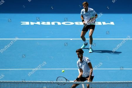 Pierre-Hugues Herbert of France (back) and Nicolas Mahut (front) of France in action against Henri Kontinen of Finland and John Peers of Australia during the men's doubles final on day fourteen of the Australian Open tennis tournament in Melbourne, Australia, 27 January 2019.