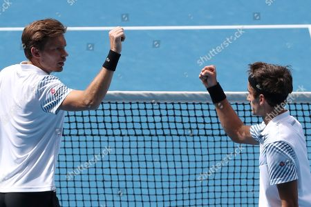 Pierre-Hugues Herbert of France (R) and Nicolas Mahut (L) of France celebrate during the match against Henri Kontinen of Finland and John Peers of Australia during the men's doubles final on day fourteen of the Australian Open tennis tournament in Melbourne, Australia, 27 January 2019.