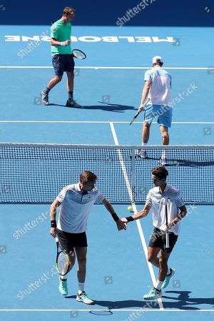 Pierre-Hugues Herbert of France (bottom, R) and Nicolas Mahut of France (bottom, L) in action against Henri Kontinen (top, L) of Finland and John Peers (top, R) of Australia  in the men's doubles final on day fourteen of the Australian Open tennis tournament in Melbourne, Australia, 27 January 2019.