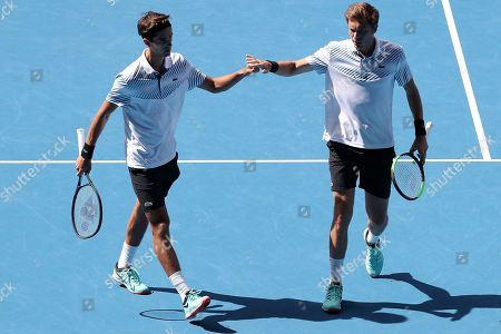 Pierre-Hugues Herbert of France (L) and Nicolas Mahut (R) of France react during the match against Henri Kontinen of Finland and John Peers of Australia in the men's doubles final on day fourteen of the Australian Open tennis tournament in Melbourne, Australia, 27 January 2019.