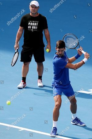 Coach Marian Vajda (L) looks on during a practice session for Novak Djokovic (R) of Serbia on day fourteen of the Australian Open tennis tournament in Melbourne, Australia, 27 January 2019.