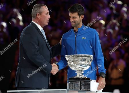 Serbia's Novak Djokovic, right, receives his trophy from Ivan Lendl after defeating Spain's Rafael Nadal in the men's singles final at the Australian Open tennis championships in Melbourne, Australia