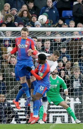 Crystal Palace's Connor Wickham, left, jumps to intercept a corner kick during an English FA Cup fourth round soccer match between Crystal Palace and Tottenham Hotspur at Selhurst Park in London