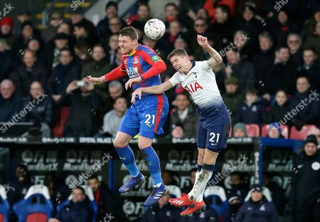 Crystal Palace's Connor Wickham jumps for the ball with Tottenham's Juan Foyth, right, during an English FA Cup fourth round soccer match between Crystal Palace and Tottenham Hotspur at Selhurst Park in London