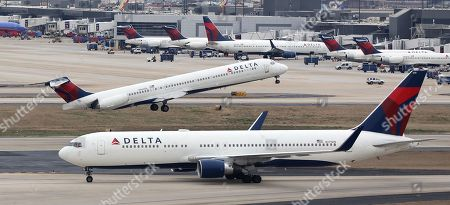A Delta Air Lines McDonnell Douglas MD-88 tail number N964DL (T) takes off for Gerald R. Ford International Airport behind a taxiing Delta Air Lines Boeing 767-300 tail number N179DN (B) at Hartsfield-Jackson Atlanta International Airport in Atlanta, Georgia, USA, 27 January 2019. Hartsfield-Jackson has been the world's busiest airport by passenger traffic since 1998 and is the primary hub for Delta Air Lines.