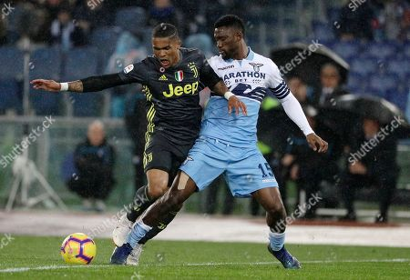 Juventus' Douglas Costa, left, challenges for the ball with Lazio's Quissanga Bastos during the Serie A soccer match between Lazio and Juventus at the Olympic stadium, in Rome