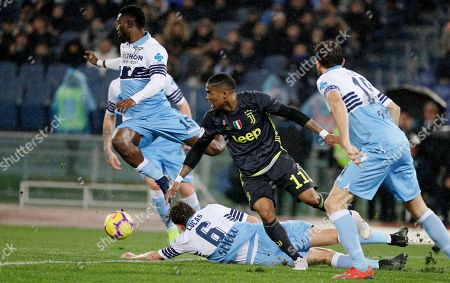 Juventus' Douglas Costa, center, is tackled by Lazio's Lucas Leiva, bottom, during the Serie A soccer match between Lazio and Juventus at the Olympic stadium, in Rome