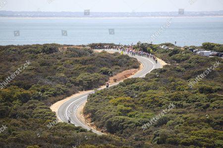 Riders ride past Bells Beach