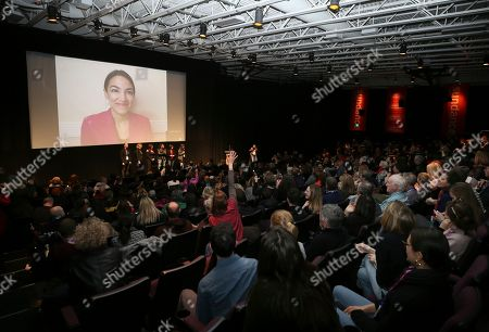 "Alexandria Ocasio-Cortez, Rachel Lears, Paula Jean Swearengin, Amy Vilela, Cori Bush. A audience member raises her hand to ask a question while Rep. Alexandria Ocasio-Cortez, D-N.Y. appears on screen in the MARC theater during a Q&A session after the premiere screening of the film ""Knock Down the House"" during the 2019 Sundance Film Festival, in Park City, Utah"