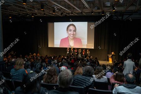 "Alexandria Ocasio-Cortez, Rachel Lears, Paula Jean Swearengin, Amy Vilela, Cori Bush. Rep. Alexandria Ocasio-Cortez, D-N.Y. smiles as she listens to an audience member's question over video conference during a Q&A session after the premiere screening of the film ""Knock Down The House"", a documentary about her as well as Paula Jean Swearengin, Amy Vilela, and Cori Bush, seen at the front with filmmaker Rachel Lears in the MARC theater during the 2019 Sundance Film Festival, in Park City, Utah"