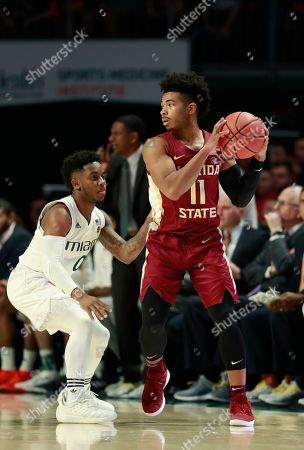 Florida State guard David Nichols (11) looks for an open teammate past Miami guard Chris Lykes (0) during the first half of an NCAA college basketball game, in Coral Gables, Fla