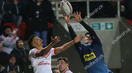 Tom Davies of Wigan Warriors and Regan Grace of St Helens reach for the high ball