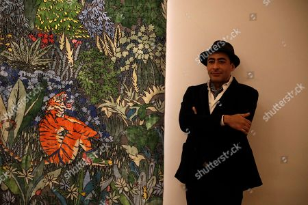 "Stock Picture of Indian-born, London-based artist Raqib Shaw poses for photographers next to his rug ""Ode to the Tigers of Bandhavgarh"" displayed as part of the ""Tomorrow's Tigers"" project sale at Sotheby's auction house in London, . The World Wide Fund for Nature project aims to raise funds and awareness to double the number of Tigers in the wild by 2022 and features rugs by 10 international artists"