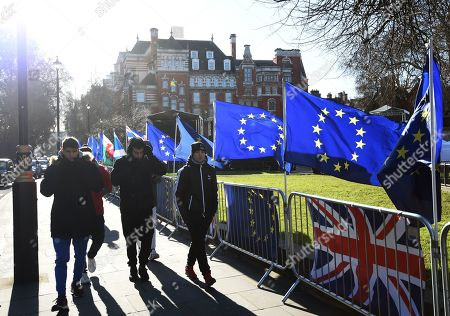 Pedestrians walk past EU flags by the Houses of Parliament in Westminster London, Britain, 28 January 2019. On 29 January British Parliament will vote on British Prime Minister Theresa May's Plan B for Brexit and discuss the next steps proposed by May and alternative plans by MEPs, including plans to delay Britain's exit on 29 March 2019 by requesting an extension of the two-year negotiation period for Article 50.