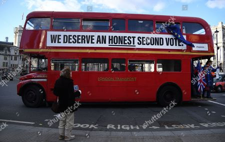 A pro EU campaign bus drives past a Vote Leave supporter outside parliament in London, Britain, 28 January 2019. The House of Commons is set to vote on British Prime Minister Theresa May's Plan B for Brexit to parliament on 29 January.