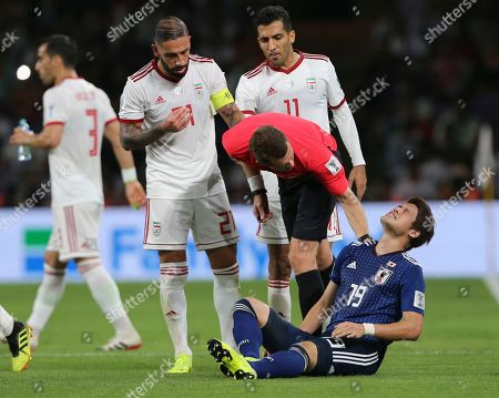 Japan's defender Hiroki Sakai grimaces in pain after a foul as Iran's Ashkan Dejagah, left, and Vahid Amiri talk to referee during the AFC Asian Cup semifinal soccer match between Iran and Japan at Hazza Bin Zayed Stadium in Al Ain, United Arab Emirates