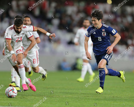 Stock Image of Japan's midfielder Genki Haraguchi in a ction to score by Iran's defender Ramin Rezaeian during the AFC Asian Cup semifinal soccer match between Iran and Japan at Hazza Bin Zayed Stadium in Al Ain, United Arab Emirates
