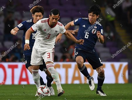Iran's midfielder Ehsan Haji Safi, center, controls the ball against Japan's defender Wataru Endo, right, during the AFC Asian Cup semifinal soccer match between Iran and Japan at Hazza Bin Zayed Stadium in Al Ain, United Arab Emirates