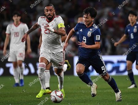 Japan's forward Takumi Minamino, might, fights for the ball with Iran's midfielder Ashkan Dejagah, left, during the AFC Asian Cup semifinal soccer match between Iran and Japan at Hazza Bin Zayed Stadium in Al Ain, United Arab Emirates