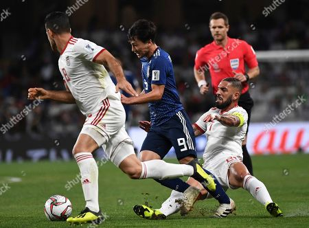 Japan's forward Takumi Minamino, center, is tackled by Iran's midfielder Ashkan Dejagah, right, as he fights for the ball with Iran's defender Morteza Pouraliganji, left, during the AFC Asian Cup semifinal soccer match between Iran and Japan at Hazza Bin Zayed Stadium in Al Ain, United Arab Emirates