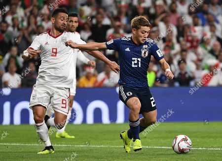 Japan's midfielder Ritsu Doan, right, fights for the ball with Iran's midfielder Omid Ebrahimi, left, during the AFC Asian Cup semifinal soccer match between Iran and Japan at Hazza Bin Zayed Stadium in Al Ain, United Arab Emirates