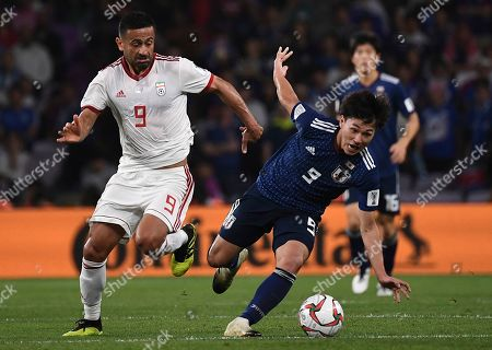Japan's forward Takumi Minamino, right, fights for the ball against Iran's midfielder Omid Ebrahimi, left, during the AFC Asian Cup semifinal soccer match between Iran and Japan at Hazza Bin Zayed Stadium in Al Ain, United Arab Emirates