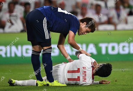 Japan's forward Yoshinori Muto, top, speaks withIran's midfielder Vahid Amiri, lies on the ground, during the AFC Asian Cup semifinal soccer match between Iran and Japan at Hazza Bin Zayed Stadium in Al Ain, United Arab Emirates