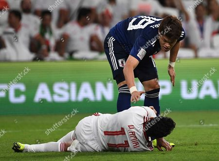 Japan's forward Yoshinori Muto, top, tires to help Iran's midfielder Vahid Amiri, lies on the ground, during the AFC Asian Cup semifinal soccer match between Iran and Japan at Hazza Bin Zayed Stadium in Al Ain, United Arab Emirates