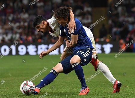 Iran's midfielder Mehdi Torabi, background, fights for the ball with Japan's forward Junya Ito, foreground, during the AFC Asian Cup semifinal soccer match between Iran and Japan at Hazza Bin Zayed Stadium in Al Ain, United Arab Emirates, . Japan beat Iran 2-0