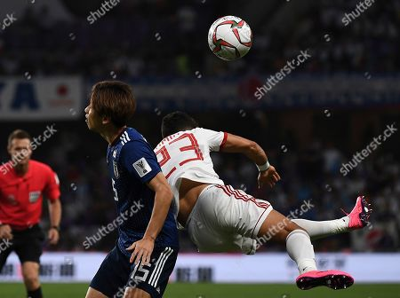 Iran's defender Ramin Rezaeian, right, fights for the ball against Japan's forward Yuya Osako, left, during the AFC Asian Cup semifinal soccer match between Iran and Japan at Hazza Bin Zayed Stadium in Al Ain, United Arab Emirates