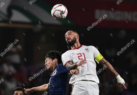 Iran's midfielder Ashkan Dejagah, right, jumps for the ball with Japan's midfielder Gaku Shibasaki, left, during the AFC Asian Cup semifinal soccer match between Iran and Japan at Hazza Bin Zayed Stadium in Al Ain, United Arab Emirates