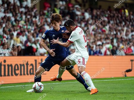 Omid Ebrahimi of Iran taking the ball away from Toshihiro Aoyama of Japan during Iran v Japan at the Hazza bin Zayed Stadium in Abu Dhabi, United Arab Emirates, AFC Asian Cup, Asian Football championship